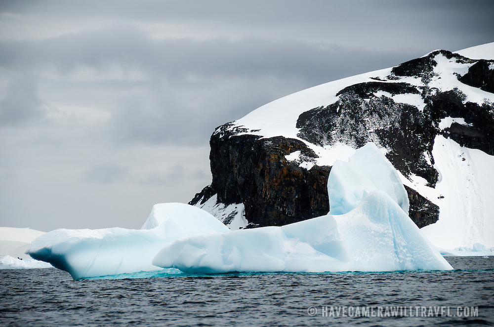 The soft shapes of some passing icebergs contrast with the rough edges of the cliffs of the mountain in the background at Trinity Island, Antarctica.