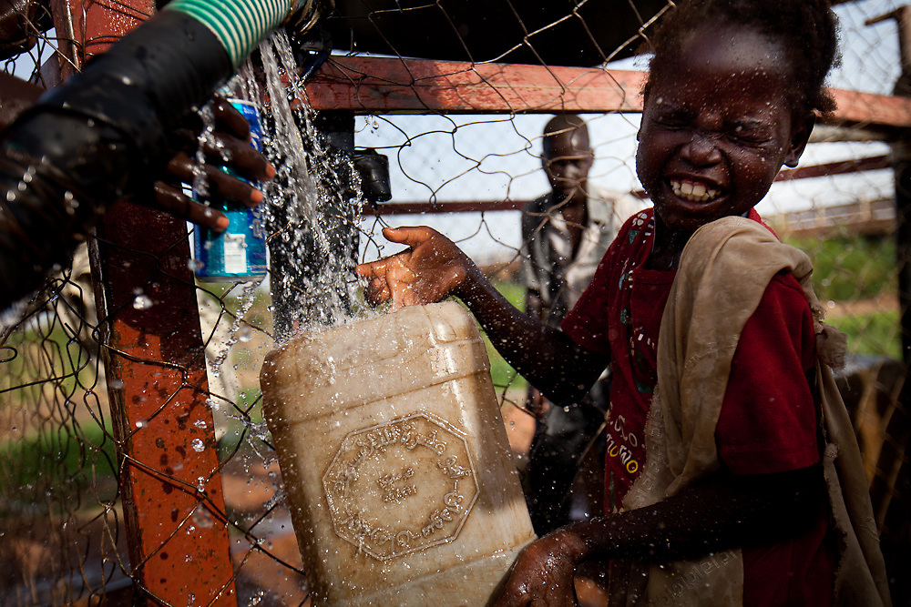 A girl fetches water at a community well in Bentiu. The well is one of the few benefits for the people of South Sudan from oil profits.