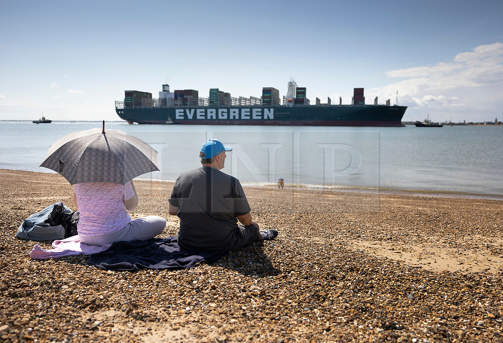 © Licensed to London News Pictures. 03/08/2021. Felixstowe, UK. People watch from the shore as the container ship 'Ever Given' arrives at the port of Felixstowe in Suffolk. The giant 400 metre long cargo ship became stuck in the Suez Canal in March causing worldwide delays to trade and was only released by the Egyptian authorities after an agreement was reached over a £655m compensation claim. Photo credit: Peter Macdiarmid/LNP
