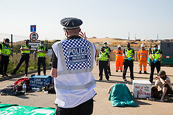 West Hyde, UK. 14th September, 2020. A Hertfordshire Police Incident Commander introduces a HS2 worker about to make a statement regarding the ownership of the property directly in front of him to environmental activists from HS2 Rebellion using lock-on arm tubes to block a gate to the South Portal site for the HS2 high-speed rail link. Anti-HS2 activists blocked two gates to the same works site for the controversial £106bn rail link, one remaining closed for over six hours and another for over nineteen hours.