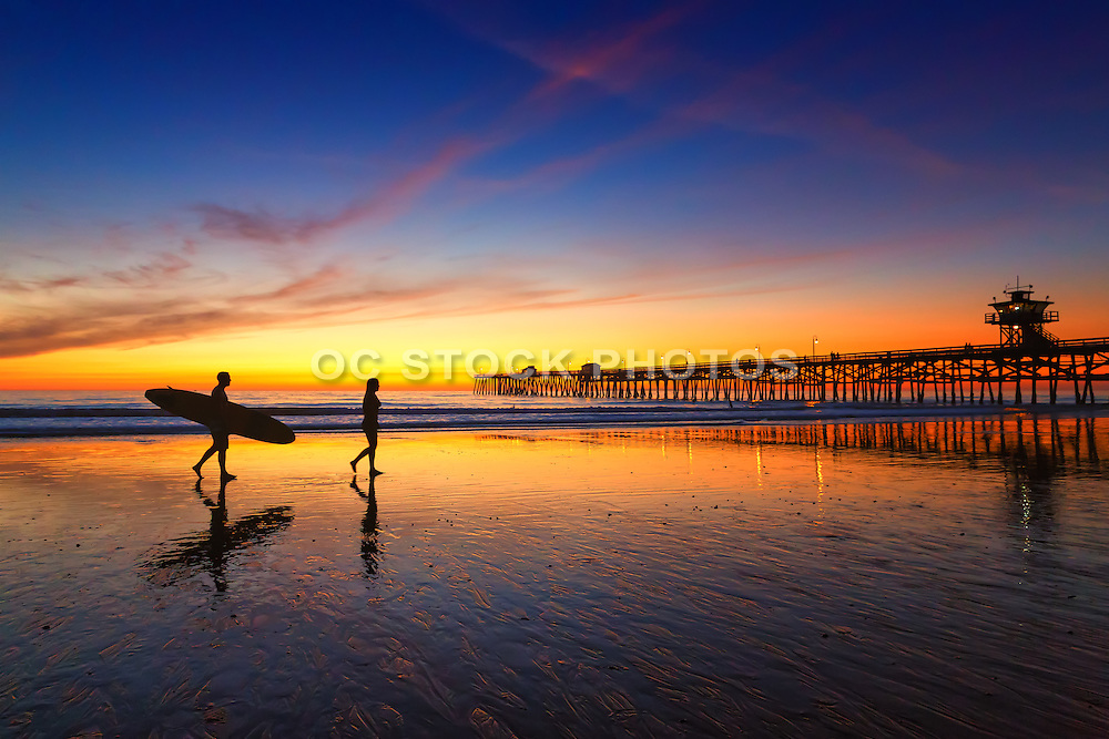 Long Board Surfer Walking at Low Tide by the San Clemente Pier at Susnet