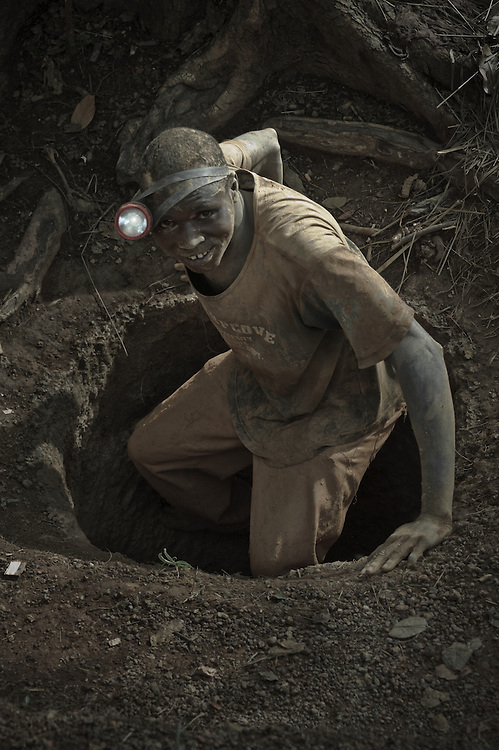 Stock photograph of an African gold miner in Guinea climbing down into his shaft for a night of mining. The night effect has been simulated by under-exposing the image and lighting the torch in Lightroom.