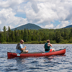 A man and woman canoeing on Saddleback Lake in Dallas Plantation, Maine. High Peaks region near Rangely.