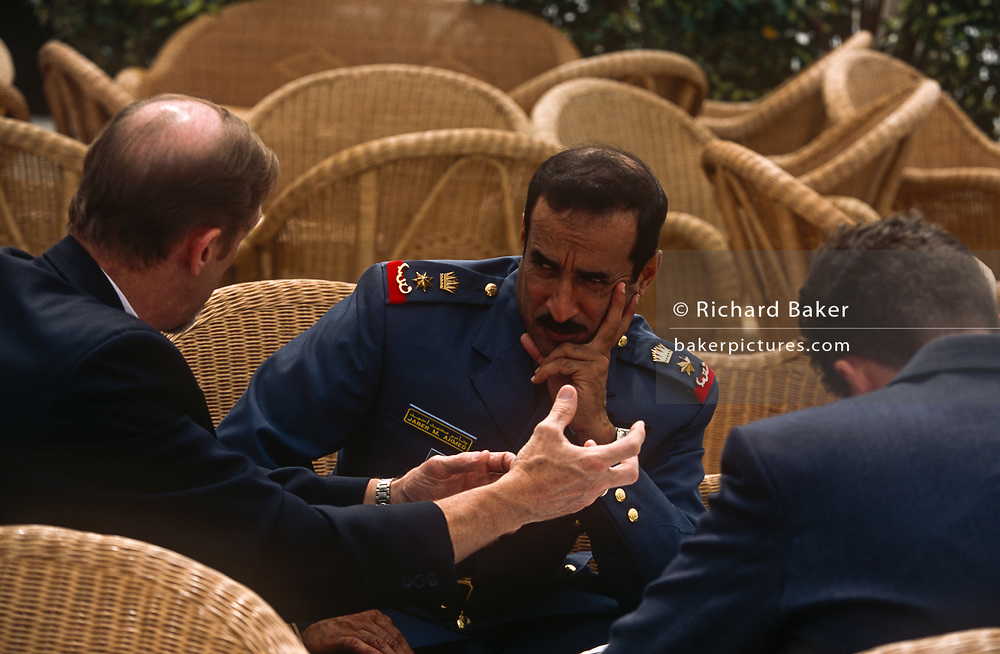 A doubtful-looking miitary officer from an unknown foreign state (possibly Kuwait) listens to an explanation from a western genleman at the BAE Systems corporate exhibition chalet during the Farnborough Air Show, on 20th June 2002, at Farnborough, Hampshire, England.