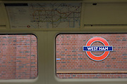 West Ham's London underground tbe station seen through carriage window of a tube train carriage.