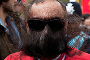 Man covers his face with his beard to protest at a demonstrator being de-masked. Demonstration by unions and other organisations of workers to mark the annual May Day or Labour Day in central London, UK.