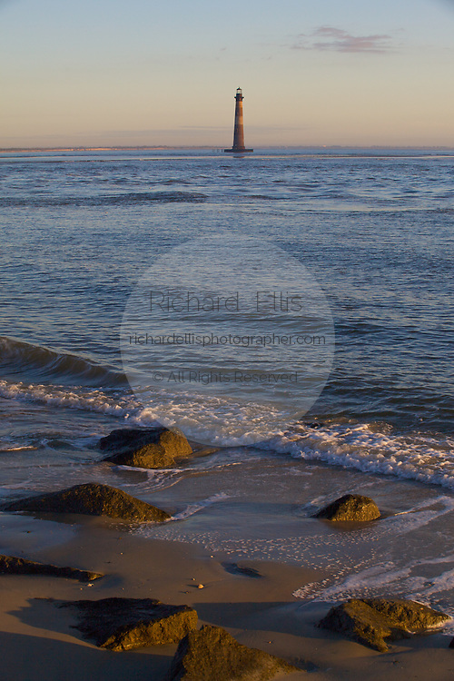 Sunrise over Folly Beach with the Morris Lighthouse near Charleston, SC. Morris Lighthouse dates back to 1767 but was rebuilt in the current form in 1873 after it was destroyed in the civil war.