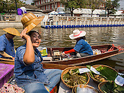 12 FEBRUARY 2015 - BANGKOK, THAILAND:  Vendors sell food to customers at a new floating market opened in Khlong Phadung Krung Kasem, a 5.5 kilometre long canal dug as a moat around Bangkok in the 1850s. The floating market opened at the north end of the canal near Government House, which is the office of the Prime Minister. The floating market was the idea of Thai Prime Minister General Prayuth Chan-ocha. The market will be open until March 1.    PHOTO BY JACK KURTZ
