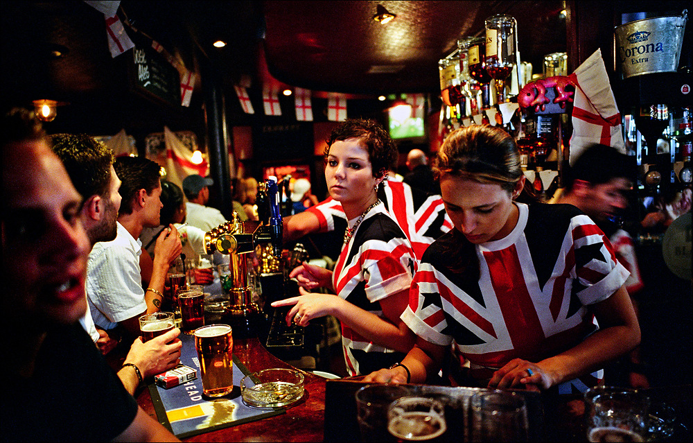 Bartenders wearing British Union Jack shirts serve sports fans the Zetland Arms pub in the London borough of South Kensington. The occasion was a EuroCup football/soccer qualifying match. © Steve Raymer / Getty Images /ALL RIGHTS RESERVED