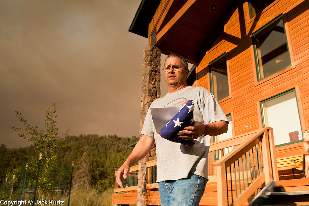 """04 JUNE 2011 - GREER, AZ: An American flag was the last thing Jim Tress (CQ) grabbed from his home in Greer before evacuating back to Tucson. The fire grew to more than 140,000 acres early Saturday with zero containment. A """"Type I"""" incident command team has taken command of the fire.    PHOTO BY JACK KURTZ"""