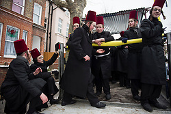 © Licensed to London News Pictures. 01/03/2018. London, UK. A group of Orthodox Jewish men in dress, climb on to the back of a truck as they celebrate the festival of Purim on the streets of Stamford Hill in north London on March 1, 2018. Purim celebrates the miraculous salvation of the Jews from a genocidal plot in ancient Persia, an event documented in the Book of Esther. Traditionally the jewish community wear fancy dress and exchange reciprocal gifts of food and drink. Photo credit: Ben Cawthra/LNP