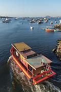 A coastal fishing boat heads out in Guanabara Bay in the Urca neighborhood in Rio de Janeiro, Brazil.