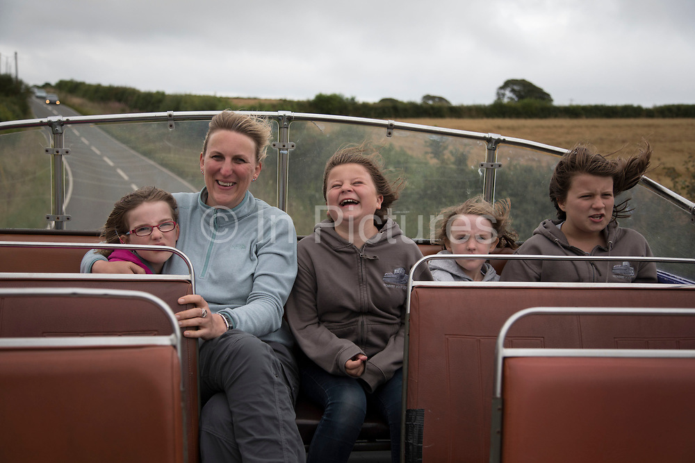 Happy family singing with a mother and her two daughters and nieces on an open top bus in Devon, England, United Kingdom. One grown up and four girls join in a sing song of 80s hits on a joyful and laughter filled journey.