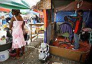 Paul Michelet, 29, gets a hair cut by barber Charilirn Charles, 25. The makeshift barber shop is seen at Haiti's only golf course now home to tens of thousands of earthquake survivors at the Petion-Ville Club golf course on March 3. 2010...