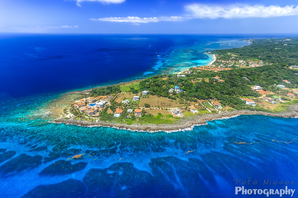 Aerial image of west end of tropical Roatan island and rthe surroundign coral reefs