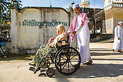 26 OCTOBER 2012 - PULASAIZ, NARATHIWAT, THAILAND:  A man and his mother leave the mosque after Eid al-Adha services in the villiage Pulasaiz, in the province of Narathiwat, Thailand. Eid al-Adha, also called Feast of the Sacrifice, is an important religious holiday celebrated by Muslims worldwide to honor the willingness of the prophet Ibrahim (Abraham) to sacrifice his firstborn son Ishmael as an act of submission to God, and his son's acceptance of the sacrifice before God intervened to provide Abraham with a ram to sacrifice instead. In 2012 Eid al-Adha was celebrated Oct 25 - 26.    PHOTO BY JACK KURTZ