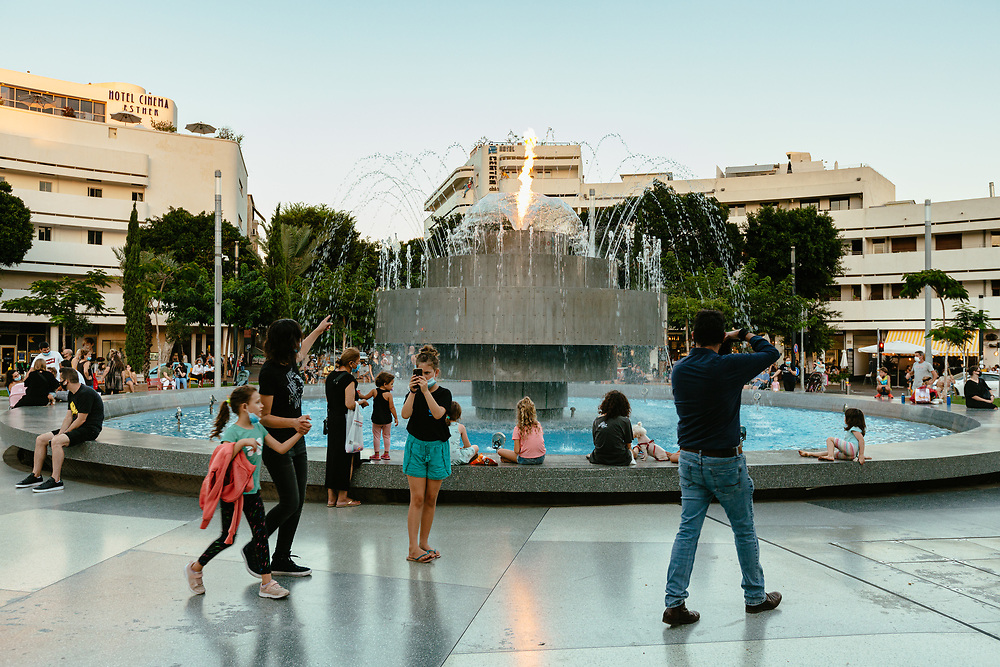 People enjoy a music, water and fire show the fountain at  the newly restored Dizengoff Square, in central Tel Aviv, Israel, on August 19, 2020.
