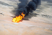 Oil industry in Ras Tanura area, Saudi Arabia,  flare fire smoke in desert 1979