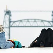 Nederland Rotterdam 20060501 Foto: David Rozing .2 meiden luieren op een van de kunstwerken naast de voet van de Erasmusbrug op de Kop van Zuid met op de achtergrond de brug de Hef..Foto David Rozing