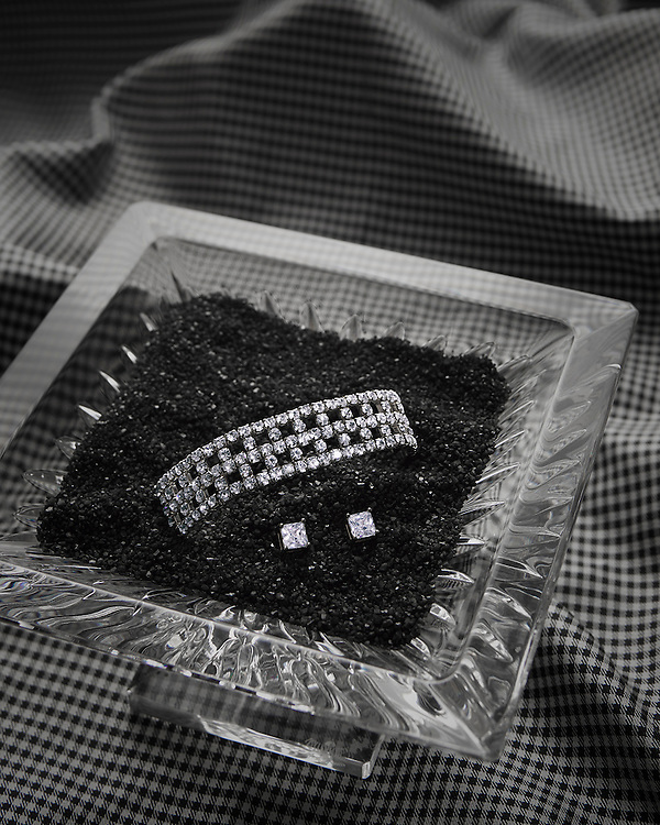 Diamond braclet & earrings in a crystal vessel with black sand and houndstooth fabric.