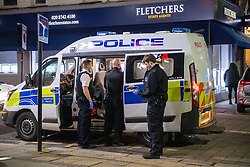 © Licensed to London News Pictures. 29/01/2021. London, UK. Officers talk to a man detained in a police van. Police were called to the Piano Restaurant on Chiswick High Road on the evening of Friday 29th after reports of a large gathering. Police forced entry through a rear door which lead to many at the gathering to flee through the main entrance at the front of the restaurant. A number of people were detained for a short period including one person held in a police van. Photo credit: Peter Manning/LNP