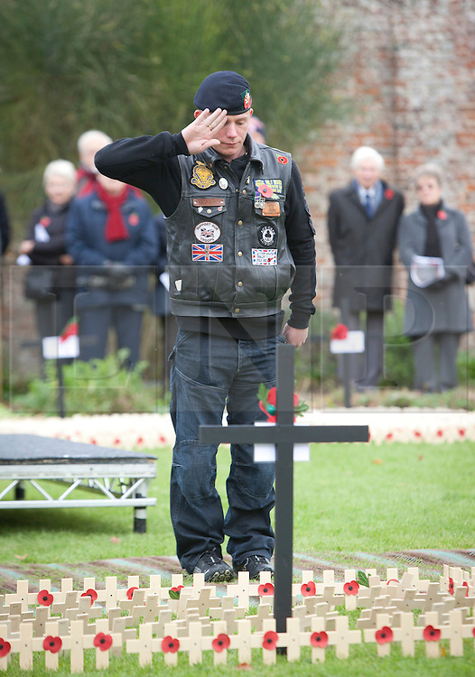 © Licensed to London News Pictures. 09/11/2012, Royal Wootton Bassett.  Former Private soldier Aron Shelton, 28, from Bridlington, East Yorkshire who had his leg amputated in 2008 following an incident in Afghanistan when the vehicle he was travelling in hit a roadside bomb, plants a cross in the Field of Remembrance today in Royal Wootton Bassett.   Photo credit : Alison Baskerville/LNP