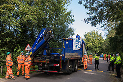 Two anti-HS2 activists with a NHS not HS2 banner, one of whom secured with a large rope around his neck, block a HGV used for works connected to the HS2 high-speed rail link on 28 September 2020 in Denham, United Kingdom. Environmental activists continue to try to prevent or delay works on the controversial £106bn project for which the construction phase was announced on 4th September from a series of protection camps based along the route of the line between London and Birmingham.