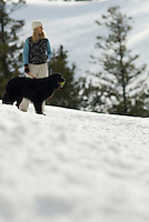 A young woman walks her dog in Jackson Hole, Wyoming (selective focus).