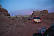Cars drive a dirt road at twilight through the San Rafael Swell, Utah.