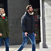 A couple of guyus take off the wearing a mask at street during Coronavirus - Pandemic hit Oxford Street many shops closure a few open but empty on 21 March 2020, UK.
