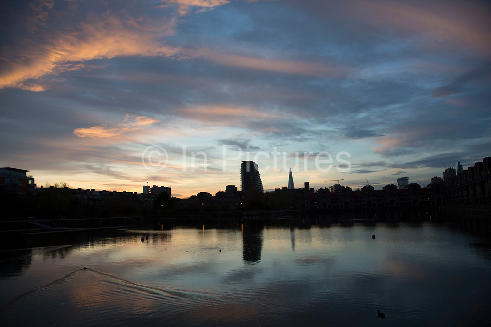 Pink and blue clouds and sky at sunset with a city skyline looking over Shadwell Basin in East London, England, United Kingdom. (photo by Mike Kemp/In Pictures via Getty Images)