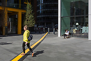 A lady crosses a yellow line that covers hazardous electrical cabling at Leadenhall in the City of London, (aka The Square Mile) the capital's financial district, on 2nd September 2019, in London, England.