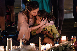 October 3, 2017 - Las Vegas, Nevada, U.S - People gather to mourn, light candles and leave items at a makeshift memorial on South Las Vegas Boulevard near the site of the Route 91 Harvest Music Fest where Sunday's mass shooting took place. At least 59 people died in the shooting and 515 people were injured Sunday night. The shooting has become the deadliest in modern U.S. history. (Credit Image: © Nick Otto via ZUMA Wire)