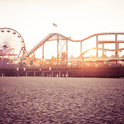 Santa Monica Pier Roller Coaster retro photo at sunset. Santa Monica Pier is a Southern California landmark that has an amusement park with a ferris wheel, roller coaster, restaurants, and other attractions. Retro photo has vintage nostalgic tone.