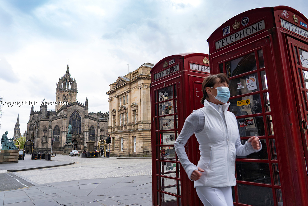 Edinburgh, Scotland, UK. 29 April 2020. Views of Edinburgh Old Town as coronavirus lockdown continues in Scotland. Streets remain deserted and shops and restaurants closed and many boarded up. Scottish Government now recommends public to wear face masks. Female jogger wearing face mask runs along a deserted Royal Mile. Iain Masterton/Alamy Live News
