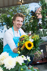 Portrait of mid adult man holding bunch of flower, smiling