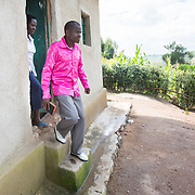 CAPTION: Jean Claude and Claudine leave home for church. Their improved financial circumstances have enabled them to spend on various things that would have been unthinkable to them before, such as smart clothing. They are grateful they have access to better and more plentiful food and safe shelter as well, and say that they feel secure and happier thanks to the programme. Jean Claude believes that their lives will continue to improve, and that poverty is now a thing of the past for them. Jean Claude is ambitious: further down the line, he intends to be in a position to buy an 18-seater minibus that he will use to transport fare-paying customers. He feels that this target is reachable even within the next four years. He plans to get someone else to drive this, as he will personally offer taxi services to foreign tourists, NGO workers and others, putting into use his English speaking skills as he's the only person in the area who knows the language. Jean Claude developed these ideas through the training he received, and says that the courses taught him a lot about investment and making one's financial resources work better. LOCATION: Kabuga Village, Gafumba Cell, Rusatira Sector, Huye District, South Province, Rwanda. INDIVIDUAL(S) PHOTOGRAPHED: Claudine Iradukunda (left) and Jean Claude Minani (right).
