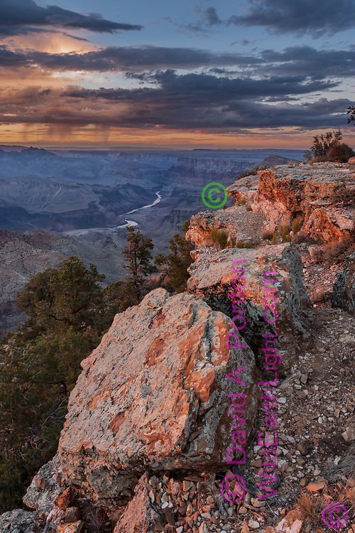 Boulders along the south rim of the Grand Canyon, with the Colorado River in the distant canyon and an evening rainstorm, Grand Canyon National Park, AZ, © David A. Ponton