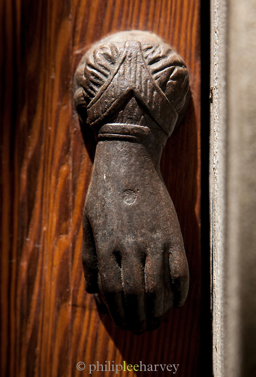 A door knocker on a wooden door in Solomeo, Umbria, Italy