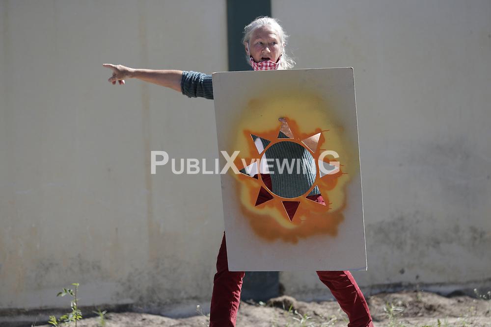 Aktivistin Jutta von dem Bussche sprüht mit einer Schablone die Wendlandspnne auf die Mauer um das Erkundungsbergwerk in Gorleben<br /> <br /> Ort: Gorleben<br /> Copyright: Andreas Conradt<br /> Quelle: PubliXviewinG