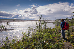 A hiker gazes on the the McKinley River at the end of the McKinley Bar Trail in Denali National Park and Preserve in Alaska. The trail which begins near Wonder Lake is used by climbers to cross the McKinley River when climbing Mt. McKinley from the north side of the mountain.