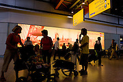 """Half-silhouetted figures add to the bustle of a hectic arrivals concourse at Heathrow Airport's Terminal 5. Seen against the orange advertisement for Mastercard which shows scenes of London that sightseers will want to visit. People wait for family to pick them up and tourists await the rest of their groups and tour guides with baggage trolleys laden with possessions. Terminal 5 has the capacity to serve around 30 million passengers a year. From writer Alain de Botton's book project """"A Week at the Airport: A Heathrow Diary"""" (2009)."""