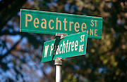 "A confusing pair of street signs showing two of the 71 Peachtree street and road names known in Atlanta. It is often joked that half of the streets in Atlanta are named Peachtree, and the other half have five names to make up for it. While ""Peachtree"" alone always refers to this street, there are 71 streets in Atlanta with a variant of ""Peachtree"" in their name.The first Peachtree was a Creek Indian village on the Chattahoochee River called Standing Peachtree. An army outpost built nearby took the name Fort Peachtree. From this has come a forest of Peachtrees. In Margaret Mitchell's epic Civil War romance Gone With the Wind, Scarlett O'Hara lives on various points of Peachtree Street along the novel."