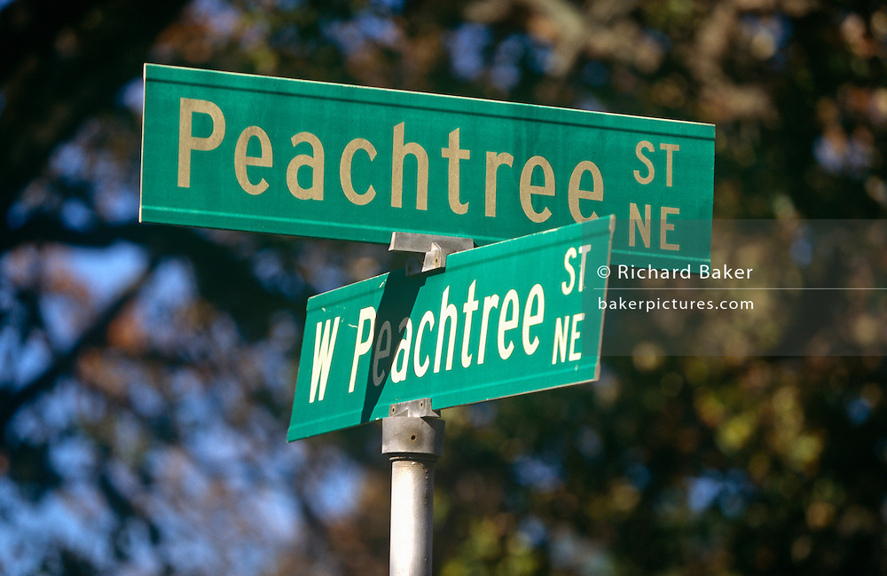 """A confusing pair of street signs showing two of the 71 Peachtree street and road names known in Atlanta. It is often joked that half of the streets in Atlanta are named Peachtree, and the other half have five names to make up for it. While """"Peachtree"""" alone always refers to this street, there are 71 streets in Atlanta with a variant of """"Peachtree"""" in their name.The first Peachtree was a Creek Indian village on the Chattahoochee River called Standing Peachtree. An army outpost built nearby took the name Fort Peachtree. From this has come a forest of Peachtrees. In Margaret Mitchell's epic Civil War romance Gone With the Wind, Scarlett O'Hara lives on various points of Peachtree Street along the novel."""