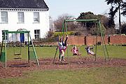 Children play village green swings, Walberswick, Suffolk