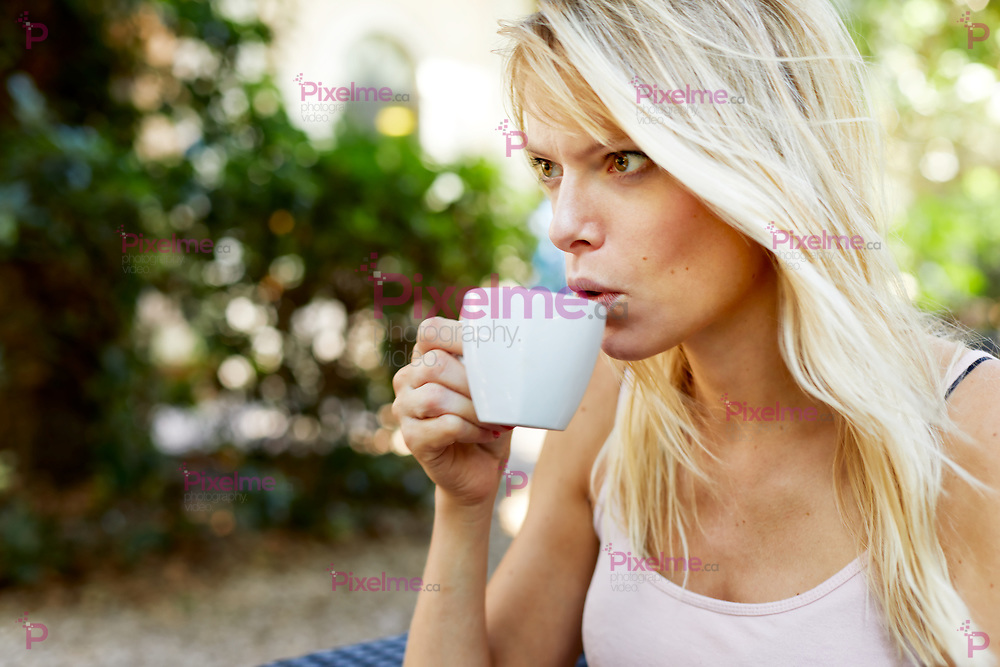 Crop view of beautiful young female with long blond hair resting in summer park with mug of hot beverage in hands and looking away
