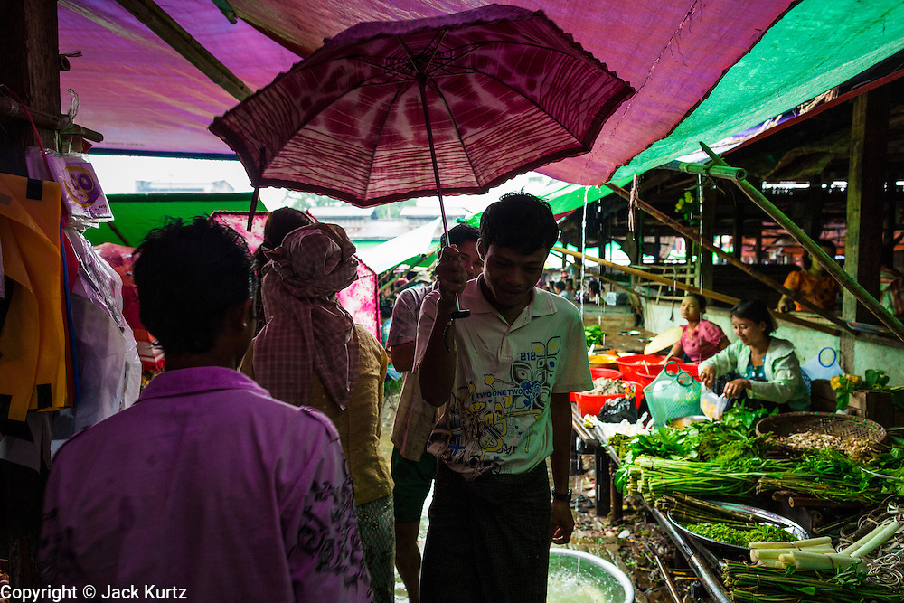 14 JUNE 2013 -  PANTANAW, AYEYARWADY, MYANMAR:  Shoppers use umbrellas to shield them from the rain in the market in Pantanaw, in the Ayeyarwady Region of south-west Myanmar. It is the hometown of former United Nations Secretary-General U Thant and of the renowned artist U Ba Nyan.  PHOTO BY JACK KURTZ