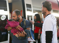 © London News Pictures. 06/09/2015. A migrant man carries his child off a train at Wien Westbahnhof train station, Vienna, Austria, September 6 2015.  Hundreds of migrants have resumed their journey through Austria to Germany after Hungary's decision on Friday to let them through. Picture by Paul Hackett/LNP