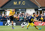 Oxford United defender Aaron Martin (6) blocks a shot from Merstham Midfielder Dan Bennett during the FA Cup match between Merstham and Oxford United at Moatside, Merstham, United Kingdom on 5 November 2016. Photo by Andy Walter.