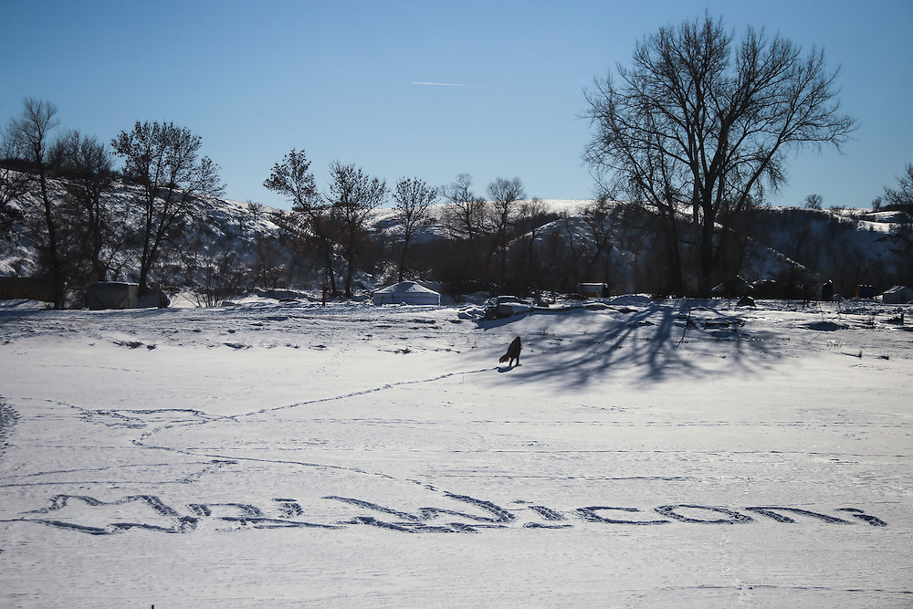 """A man walks across the frozen Cannonball River where the phrase, """"Mni Wiconi,"""" translating to """"Water is life,"""" is engraved in footprint at the Oceti Oyate Camp in Cannon Ball, North Dakota in January 2017.<br /> <br /> The US Army Corps of Engineers granted the final easement needed to complete the construction of the controversial Dakota Access Pipeline in a court filing on February 7th, 2017. An environmental impact statement that was delaying efforts to grant an easement was also terminated by the Army Corps."""